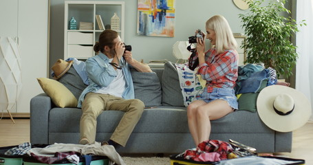 Happy young good looking couple sitting on the sofa in the cozy living room among mess as their packing suitcases for travelling and taking photos of each other with cameras.