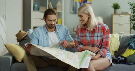 Portrait shot of the young girlfriend and boyfriend sitting at home on the couch and choosing a destination for holidays with a map in hands.