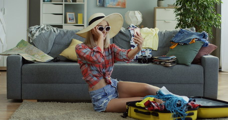 Young caucasian beautiful woman in hat and sunglasses posing to the smartphone camera while taking selfie photo on the floor at home while packing for summer vacation.