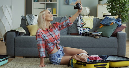 Attractive and happy young Caucasian woman taking selfie photos on the camera while sitting on the floor among mess before traveling.