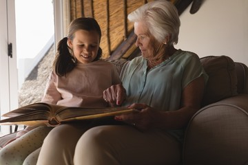 Grandmother and granddaughter looking at photo album