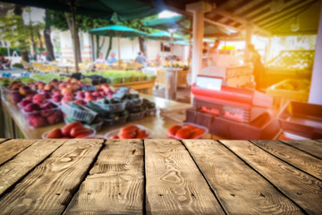 Wooden table on the street market among fresh vegetables and fruits