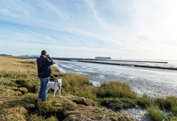 fotografierender Mann mit Hund allein an der Nordseeküste bei Bremerhaven