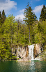 Beautiful waterfall surrounded by emeral waters and green forest, Plitvice Lakes National Park, Croatia