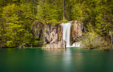 Beautiful waterfall plunging into cristal-clear emerald pond, Plitvice Lakes National Park, Croatia. Long exposure.