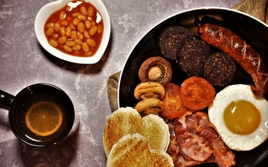 Full english breakfast: egg,bacon,tomatoes,sausage,black pudding,mushrooms,beans in tomato sauce,tea and  toast with a heart shape. Valentine`s day breakfast symbol.