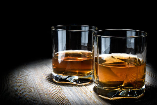 Two glasses of whiskey on a vintage wooden table on a black background.