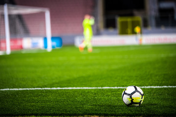 Football, soccer photo. Ball on the green grass and football goalkeeper in background