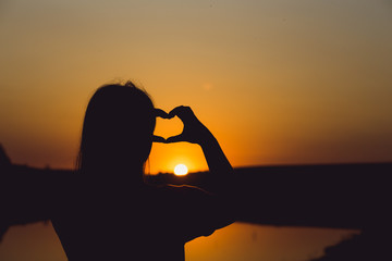 girl shows heart with fingers at sunset close up