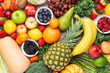 Healthy fruits vegetables background filled with strawberries raspberries oranges plums apples kiwis grapes broccoli cauiliflower mango persimmon pineapple