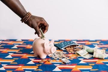 Man adding money to piggy bank