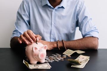 Man adding coins in piggy bank