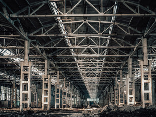 Large hall of abandoned and ruined factory or industrial warehouse inside with perspective