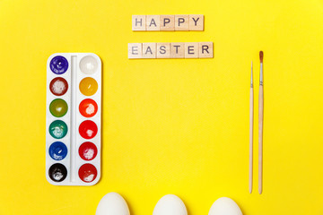 Happy Easter concept. Preparation for holiday. Inscription HAPPY EASTER letters eggs colorful paints isolated on trendy yellow background. Simple minimalism flat lay top view copy space