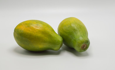 close up of two ripe green and yellow papayas isolated on white