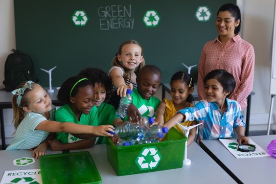 Schoolkids putting bottles in recycle container at desk in