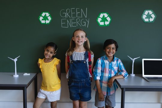Smiling schoolkids standing against green energy board in