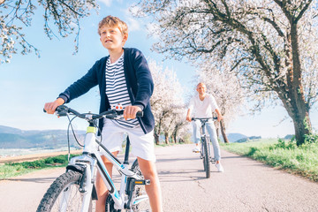 Father and son having fun when riding bicycles on country road under blossom trees. Healthy sporty lifestyle concept image.
