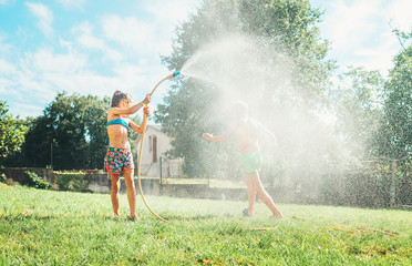 Hot summer days activity: happy little girl jumps under water, when brother pours her from garden hose