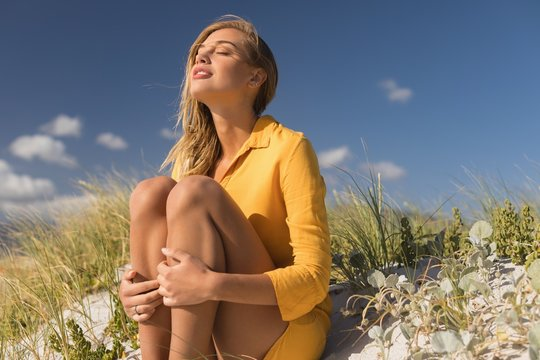 Woman sitting with eyes closed at beach