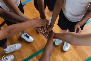 Schoolkids forming hand stack at basketball court