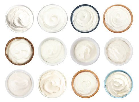Set of delicious sour cream in bowls on white background, top view