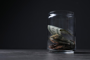 Donation jar with money on table against dark background. Space for text