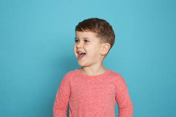 Portrait of little boy laughing on color background