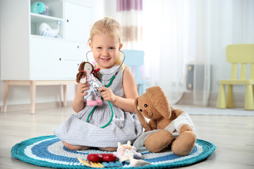Cute child imagining herself as doctor while playing with stethoscope and toy at home