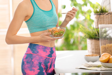 Young woman in fitness clothes having healthy breakfast at home, closeup