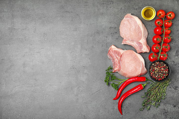 Flat lay composition with raw meat and space for text on grey background