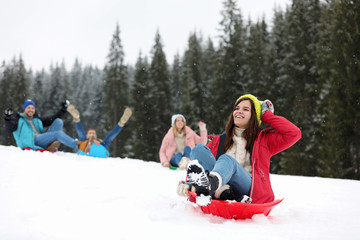 Happy friends sliding on sleds outdoors. Winter vacation