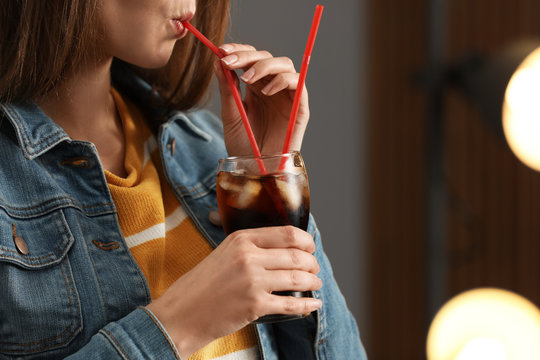 Woman drinking cola from glass against blurred background, closeup