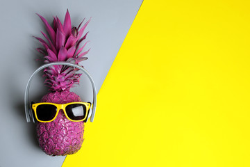 Pineapple with headphones and sunglasses on color background, top view with space for text