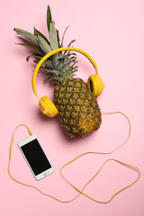 Pineapple with headphones and smartphone on color background, top view