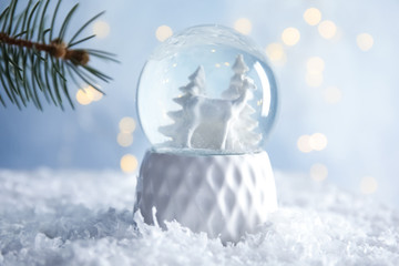 Glass globe with deer and trees on artificial snow