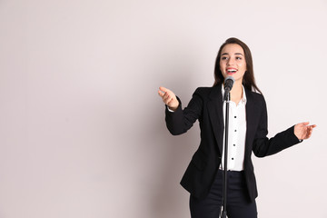 Young businesswoman with microphone on color background. Space for text