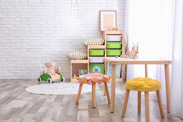 Modern eco style interior of child room with wooden crates near brick wall