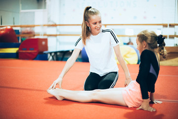 Foto auf Acrylglas Gymnastik Coach talking with a young gymnast