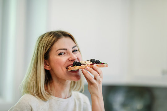 Woman having a toast with blackberry jam and vegan cream cheese