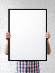 Holding frame mockup. Photo Mockup. The man hold frame. For frames and posters design. Frame size 20x28 (50x70cm).