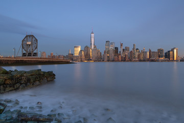 View on financial District at twilight from Hudson river beach with long exposure