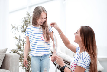 attentive mother and daughter make measurements for new clothes