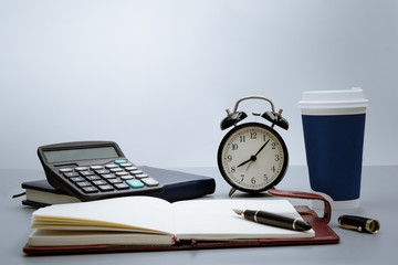alarm clock with notebook, calculator, pen and cup of coffee on gray background on working table