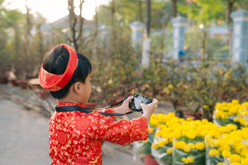 Child with digital compact camera outdoors. Cute little Vietnamese boy in ao dai dress. Tet holiday