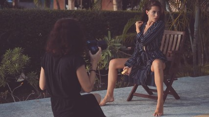 Wall Mural - woman poses for female photographer on a chair by a pool