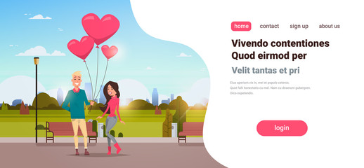 man giving woman pink heart shape air balloons happy valentines day concept young couple in love over city urban park cityscape background horizontal copy space