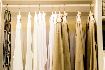 Fashionable clothes hanging on rack at modern dressing room.Toned image.Wardrobe full of Many blouses on hangers in the dressing room.Dressing closet with clothes arranged on hangers and shelf.