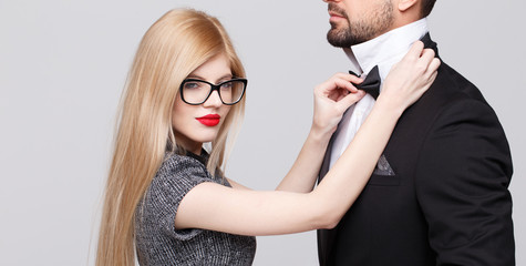 Blonde woman adjusting tie bow for man