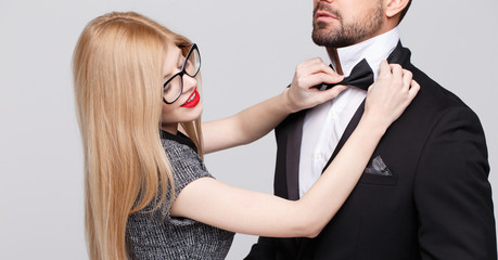 Blonde woman adjusting tie bow for man on tuxedo